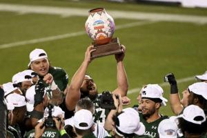ASSOCIATED PRESS                                 Hawaii linebacker Darius Muasau (53) holds up the trophy after the team's 28-14 win over Houston in the New Mexico Bowl.
