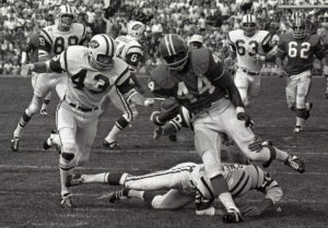 ASSOCIATED PRESS / SEPTEMBER 1969 Denver Broncos' Floyd Little avoids the tackle of New York Jets' Steve O'Neal (20) during a football game in Denver in 1969. Little, the Hall of Fame running back who starred at Syracuse and for the Denver Broncos, died Friday.