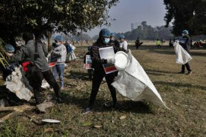 Volunteers wearing face masks as a precaution against the coronavirus clear the debris left over by tourists at Maidan, the city's largest open space in Kolkata, India, today.