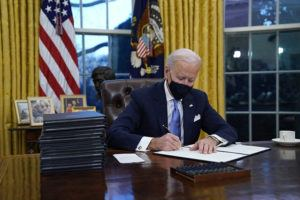ASSOCIATED PRESS                                 President Joe Biden signs his first executive order in the Oval Office of the White House in Washington.