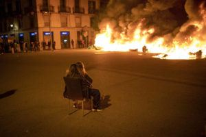 ASSOCIATED PRESS / FEB. 19                                 Two woman sit on a chair in front of burning barricades made by demonstrators during a protest condemning the arrest of rap singer Pablo Hasél in Barcelona, Spain. Violent street protests over the imprisonment of a rapper have erupted for a fourth straight night in Spain. Police in the northeastern region of Catalonia said some protesters pelted officers with bottles, stones, fireworks and paint on Friday.