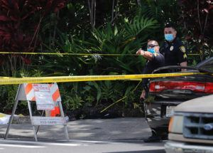 JAMM AQUINO / JAQUINO@STARADVERTISER.COM                                 Honolulu police officers stood near the scene of a fatal stabbing at the intersection of Hahaione Street and Hawaii Kai Drive Tuesday morning.