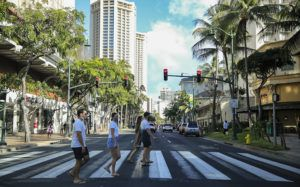 JAMM AQUINO / MARCH 7                                 Pedestrians wearing face masks cross Kalakaua Avenue on Sunday.