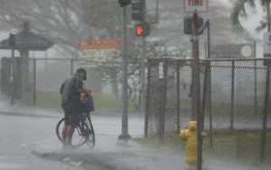 JAMM AQUINO / JAQUINO@STARADVERTISER.COM                                 A man is caught in heavy downpour along Kamehameha Highway on Wednesday in Kaneohe. A week of heavy rain storms throughout the state has saturated the ground in many areas and raised stream levels, increasing the possibility of more flooding today.