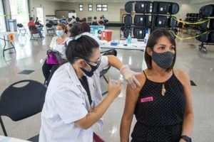CRAIG T. KOJIMA / MARCH 25                                 Cindy Khanphaphanh of Times Pharmacy administers the Johnson & Johnson vaccine to Paige Iwanaga at the Mililani Town Association Recreation Center 5.