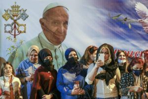ASSOCIATED PRESS                                 Women wait outside the Chaldean Cathedral of Saint Joseph, in Baghdad, Iraq, where Pope Francis, depicted on a giant poster at their back, is concelebrating a mass. Earlier today Francis met privately with the country's revered Shiite leader, Grand Ayatollah Ali al-Sistani.