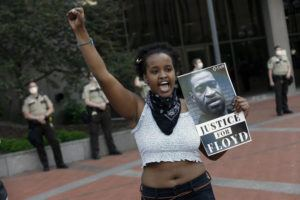 ASSOCIATED PRESS / 2020                                 A protester holds a photo of George Floyd during a protest at the Hennepin County Government Center, as protests continue over the death of Floyd, who died in police custody Monday night in Minneapolis, after video shared online by a bystander showed a white officer kneeling on his neck during his arrest as he pleaded that he couldn't breathe. Dozens of people gathered in front of the Minnesota governor's mansion on Saturday, March 6, to demand accountability for police officers, days before a former Minneapolis officer is scheduled to go on trial in the death of George Floyd.