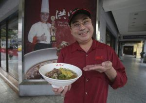 ASSOCIATED PRESS                                 Chef Hung shows pineapple beef noodle outside of his restaurant in Taipei, Taiwan, today.