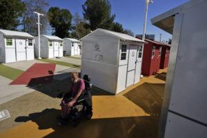 ASSOCIATED PRESS / FEBRUARY 25                                 A homeless person, who calls himself Tiffany, rides by a row of tiny homes in the North Hollywood section of Los Angeles.
