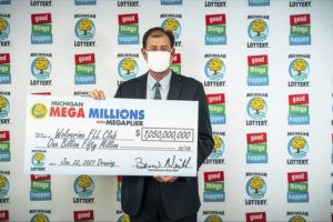 MICHIGAN LOTTERY VIA ASSOCIATED PRESS                                 Attorney Kurt Panouses posed with a check, Feb. 26, on behalf of the winners of a Mega Millions lottery jackpot in Lansing, Mich. Four people in a suburban Detroit lottery club have won a $1.05 billion Mega Millions lottery jackpot and will share $557 million after taxes.