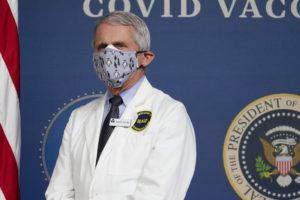 """ASSOCIATED PRESS                                 Dr. Anthony Fauci, director of the National Institute of Allergy and Infectious Diseases, listens as President Joe Biden speaks during an event to commemorate the 50 millionth COVID-19 shot in Washington on Feb. 25. Fauci said today he wishes former President Donald Trump would use his popularity among Republicans to persuade his followers to get the COVID-19 vaccine. In a round of interviews on the morning news shows, Fauci lamented polling showing that Trump supporters are more likely to refuse to get vaccinated, saying politics needs to be separated from """"commonsense, no-brainer"""" public health measures."""