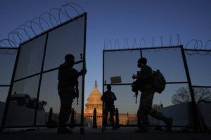 ASSOCIATED PRESS                                 National Guard soldiers open a gate of the razor wire-topped perimeter fence around the Capitol to allow a colleague in at sunrise in Washington, today.