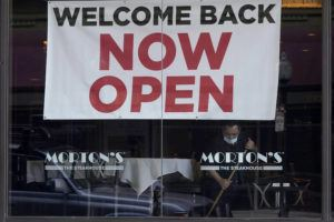 """ASSOCIATED PRESS / MARCH 4                                 A sign reading """"Welcome Back Now Open"""" is posted on the window of a Morton's Steakhouse restaurant as a man works inside during the coronavirus pandemic in San Francisco."""