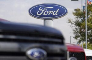 ASSOCIATED PRESS / 2020                                 The company logo hangs over a row of 2020 F-150 pickup trucks at a Ford dealership, in Denver.
