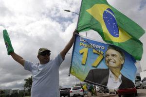 ASSOCIATED PRESS                                 A demonstrator carries a Brazilian flag and a flag with an image of Brazil's President Jair Bolsonaro during a caravan celebrating Bolsonaro's 66th birthday, in Brasilia, Brazil, Sunday.