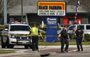 """STEPHEN KATZ /THE VIRGINIAN-PILOT VIA AP                                 Virginia Beach police put up police tape across Pacific Ave. at the Oceanfront on Saturday morning after a fatal shooting the night before in Virginia Beach, Va. A pair of overnight fatal shootings along the beachfront in Virginia Beach wounded several people in a scene described by authorities on Saturday as """"very chaotic."""""""