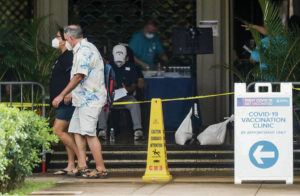JAMM AQUINO / JAQUINO@STARADVERTISER.COM                                 A man and woman Monday walked past a COVID-19 vaccination clinic at the Blaisdell Concert Hall.