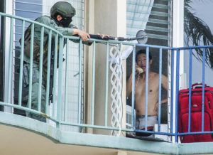 CRAIG T. KOJIMA / CKOJIMA@STARADVERTISER.COM An officer from the Honolulu Police Department uses a mirror to monitor the actions of a suspect today in Waikiki. The man, seen here on the phone, was subdued a few minutes later by police using a loud explosive device to enter the apartment at 1909 Ala Wai Blvd.