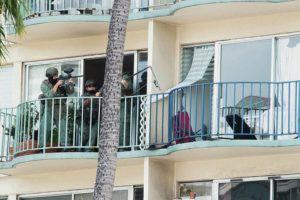 CRAIG T. KOJIMA / CKOJIMA@STARADVERTISER.COM                                 Police on an adjacent balcony prepared Thursday to enter the Waikiki apartment where a man had barricaded himself. More photos are available at staradvertiser.com.