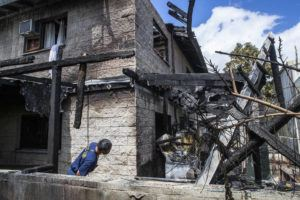 CINDY ELLEN RUSSELL / CRUSSELL@STARADVERTISER.COM                                 An HFD captain looks at the damage at 907 Winant Street on Monday.
