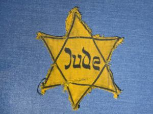 """ASSOCIATED PRESS                                 The Yellow Star badge of Heinz-Joachim Aris (Dresden 1941) reading """"Jew""""is displayed in a showcase during a press preview in the new special exhibition 'Shoes of the Dead - Dresden and the Shoah' at the Military History Museum in Dresden, Germany, in 2014. Before local anti-Jewish laws were enacted, before neighborhood shops and synagogues were destroyed, and before Jews were forced into ghettos, cattle cars, and camps, words were used to stoke the fire of hate."""