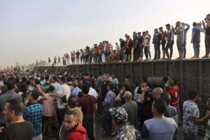 ASSOCIATED PRESS                                 People gather at the site where a passenger train derailed injuring at least 100 people, in Banha, Qalyubia province, Egypt, today. At least eight train wagons ran off the railway, the provincial governor's office said in a statement.
