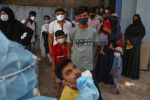 ASSOCIATED PRESS                                 A health worker takes a mouth swab sample of a man to test for COVID-19 as others wait their turn to get tested at a hospital in Hyderabad, India, today.