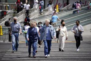 ASSOCIATED PRESS                                 Masked and unmasked pedestrians walk across Las Vegas Boulevard in Las Vegas.