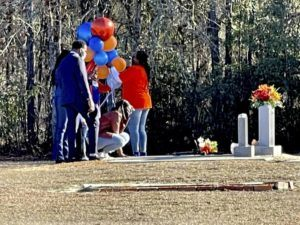 ASSOCIATED PRESS                                 Wanda Cooper-Jones knelt before the grave of her son, Ahmaud Arbery, Feb. 23, at the New Springfield Baptist Church in Waynesboro, Ga., to mark the one-year anniversary of Ahmaud Arbery's death in Brunswick, Ga. The Justice Department announced federal hate crime charges, today, in the death of Arbery, who was killed while out for a run.