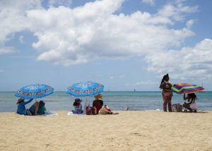 CINDY ELLEN RUSSELL / CRUSSELL@STARADVERTISER.COM                                 Hawaii has seen a big surge in travel demand over the last weeks. Here, beach-goers keep their distance from each other as they sit under their umbrellas at Queens Beach in Waikiki on Friday.