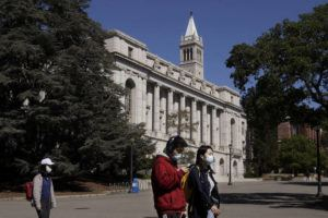 ASSOCIATED PRESS / 2020                                 People wear masks while walking past Wheeler Hall on the University of California campus in Berkeley, Calif.