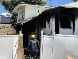 ROSEMARIE BERNARDO / RBERNARDO@STARADVERTISER.COM                                 A Honolulu Fire inspector assesses the damage after a fire was extinguished at a home in the Diamond Head area.