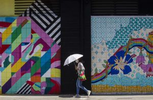 CINDY ELLEN RUSSELL / MAY 18                                 A masked woman carries an umbrella while walking along Cooke Street in Kakaako.
