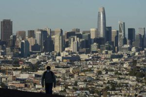 ASSOCIATED PRESS                                 A person wearing a protective mask walked in front of the skyline on Bernal Heights Hill, Dec. 7, during the coronavirus pandemic in San Francisco. California's population has declined for the first time in its history.
