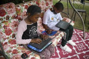 ASSOCIATED PRESS                                 Fourth-grader Sammiayah Thompson, left, and her brother, third-grader Nehemiah Thompson, worked outside, in June 2020, in their yard on laptops provided by their school system for distance learning in Hartford, Conn. Americans can begin applying for $50 off their internet bill, today, as part of an emergency government program to keep people connected during the pandemic.
