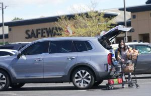 ASSOCIATED PRESS                                 A shopper wearing a face mask loaded her purchases into a sport utility vehicle, Wednesday, outside a Safeway grocery store in Aurora, Colo. Many workers in retail sales jobs who are fully vaccinated are concerned about risks posed as retailers change their mask-wearing policies for customers.