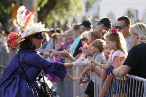 """ASSOCIATED PRESS / MAY 21                                 A woman dressed in period costume hands a trinket to a child during a parade dubbed """"Tardy Gras,"""" to compensate for a canceled Mardi Gras due to the COVID-19 pandemic, in Mobile, Ala."""