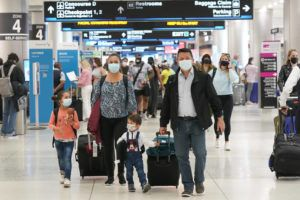 ASSOCIATED PRESS                                 Henry Hernandez, his wife Karina Gonzalez and their children Jose Sebastian, 2, and Laura, 6, of Colombia, walk towards the baggage claim area at Miami International Airport in Miami. The couple were surprised to be offered the Johnson & Johnson COVID-19 vaccine upon arrival to the U.S. It is their first overseas trip since the pandemic began last year. Florida's Emergency Management Agency is running the program through Sunday.