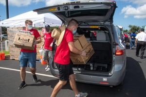 CRAIG T. KOJIMA / CKOJIMA@STARADVERTISER.COM                                 Volunteers Mark Weisbecker, left, Chris Espino and Benjamin Walters carried boxes of food to waiting cars on Friday at the Salvation Army's Kroc Center in Kapolei. The economic upheaval from the pandemic has greatly increased food insecurity in Hawaii.