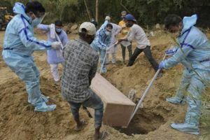 ASSOCIATED PRESS                                 Relatives bury the body of a COVID-19 victim at a graveyard in New Delhi, India.