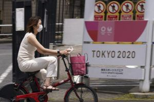 ASSOCIATED PRESS                                 A woman wearing a protective mask rides a bicycle past a banner for the Tokyo 2020 Olympic and Paralympic Games in Tokyo.