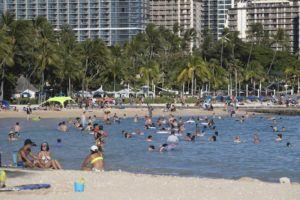 CINDY ELLEN RUSSELL / JUNE 21                                 Beachgoers gather along Waikiki Beach near the Hilton Hawaiian Village Waikiki Beach Resort. Beginning July 8, Hawaii will allow fully vaccinated travelers from the mainland U.S. to bypass pre-travel testing and quarantine rules.