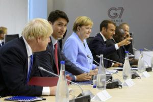 THE CANADIAN PRESS VIA AP                                 Canadian Prime Minister Justin Trudeau, second from left, sits between British Prime Minister Boris Johnson, left, and German Chancellor Angela Merkel as they take part in a meeting at the G7 Summit in Biarritz, France, in 2019. Gesturing at right is French President Emmanuel Macron.