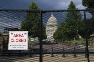 ASSOCIATED PRESS                                 The U.S. Capitol is seen under dark skies in Washington Tuesday as barriers remain six months after the Jan. 6 attack.