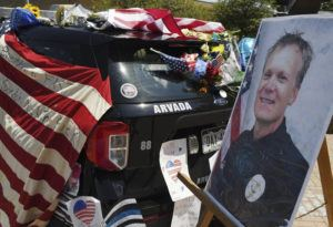 RJ SANGOSTI/THE DENVER POST VIA ASSOCIATED PRESS                                 Flowers, flags and notes covered a patrol car and bike outside Arvada City Hall during a memorial for Arvada Police Officer Gordon Beesley, Tuesday, in Arvada, Colo. Officer Beesley was killed during a shooting in Olde Town Arvada.