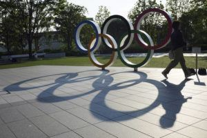 ASSOCIATED PRESS                                 A woman walks by the Olympic Rings near the National Stadium in Tokyo.