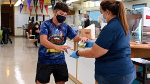 COURTESY HAWAII DEPARTMENT OF HEALTH                                 Yadyn Dowsett, 13, a student at Waianae Intermediate School, receives a free can of Spam after getting vaccinated.