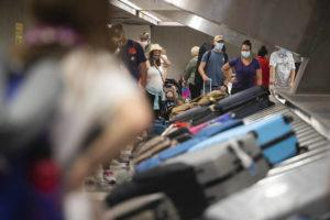 CINDY ELLEN RUSSELL / JULY 19                                 Travelers wait for their luggage at the baggage claim in Terminal 2 at Daniel K. International Airport on Monday.