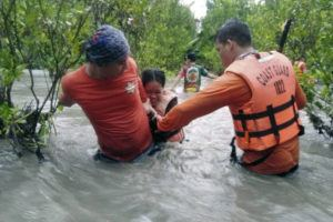 PHILIPPINE COAST GUARD VIA AP                                 In this photo provided by the Philippine Coast Guard, residents wade along floodwaters as they are evacuated to safer grounds in Naujan, Oriental Mindoro province, central Philippines. Thousands of residents fled from flooded communities and swollen rivers in the Philippine capital and outlying provinces Saturday after days of torrential monsoon rains, which left at least one villager dead, officials said.