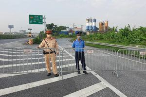 ASSOCIATED PRESS                                 Policemen guard behind barricades set up to control the traffic in Hanoi, Vietnam. Vietnam announced a 15-day lockdown in the capital Hanoi starting Saturday as a coronavirus surge spread from the southern Mekong Delta region.